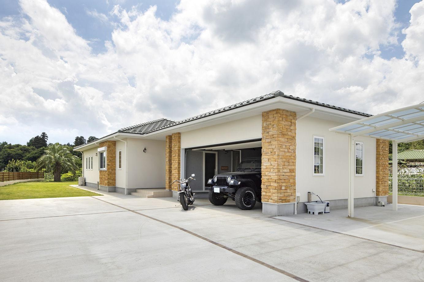 ガーデニングやアウトドアライフを満喫できる広めのスペースを確保した平屋のガレージハウスの外観の画像