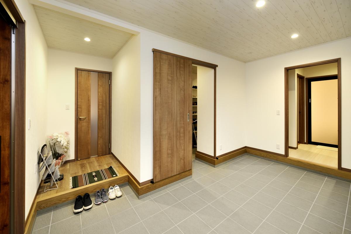 ナチュラルな白壁とダークブラウンのドアがおしゃれな土間玄関