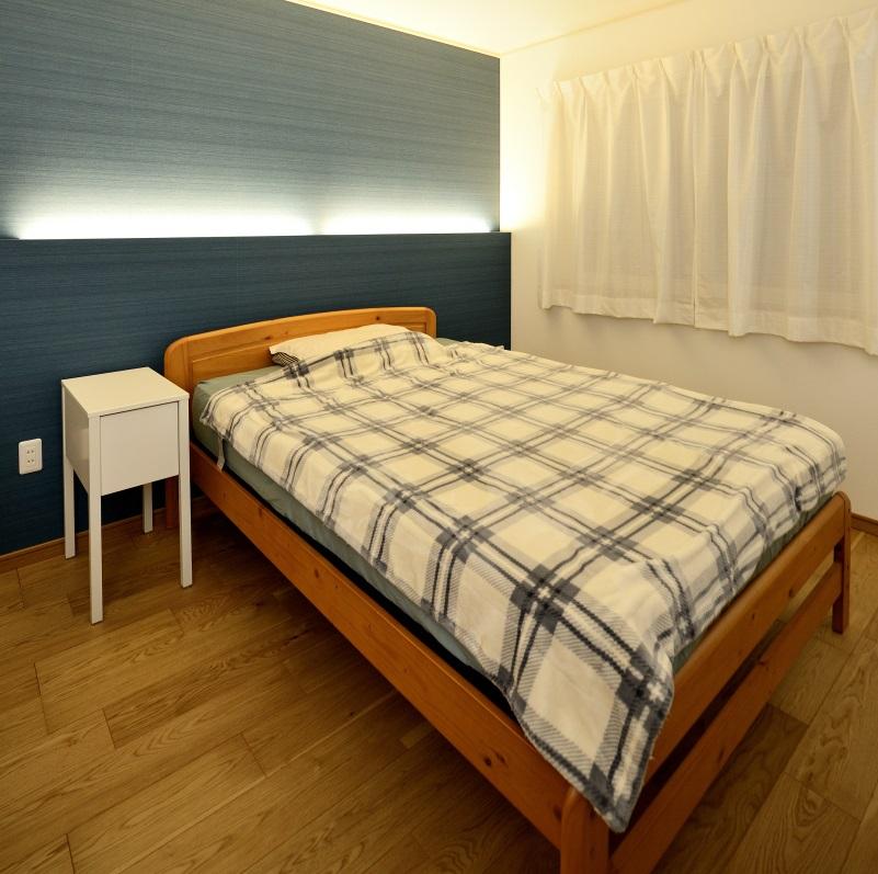 ブルーのアクセントクロスに建築家照明で雰囲気のある寝室
