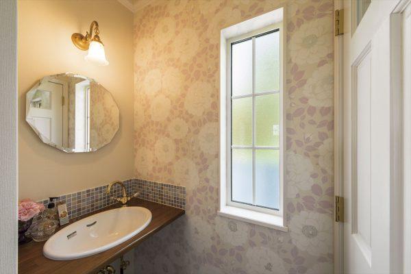 花柄のアクセントクロスや丸い鏡がおしゃれなトイレ