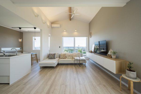 切妻屋根のカタチを活かした開放的な勾配天井のあるリビング~ホワイト×ライトグレー、ブラウンのコーディネートが素敵